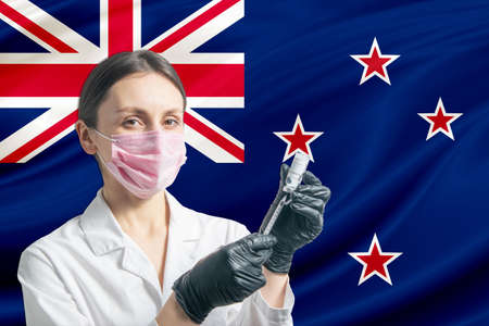 Girl doctor prepares vaccination against the background of the New Zealand flag. Vaccination concept New Zealand.