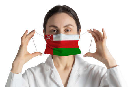 Respirator with flag of Oman Doctor puts on medical face mask isolated on white background.