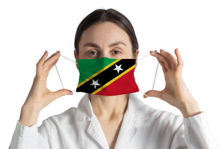 Respirator with flag of St. Kitts and Nevis Doctor puts on medical face mask isolated on white background. 免版税图像
