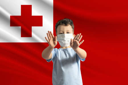 Little white boy in a protective mask on the background of the flag of Tonga. Makes a stop sign with his hands, stay at home Tonga.