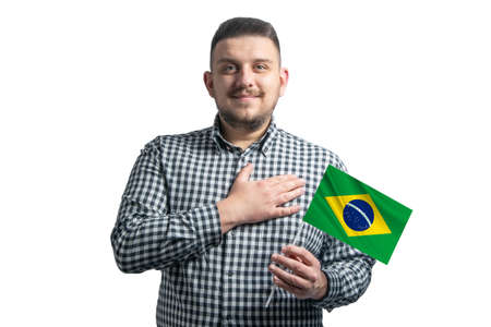 White guy holding a flag of Brazil and holds his hand on his heart isolated on a white background With love to Brazil. 免版税图像