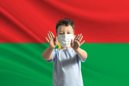 Little white boy in a protective mask on the background of the flag of Burkina Faso. Makes a stop sign with his hands, stay at home Burkina Faso.