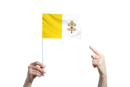 A beautiful female hand holds a Vatican flag to which she shows the finger of her other hand, isolated on white background. 免版税图像