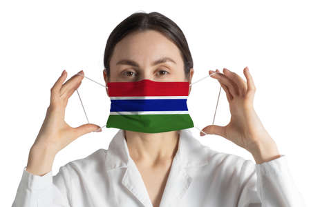 Respirator with flag of Gambia Doctor puts on medical face mask isolated on white background.