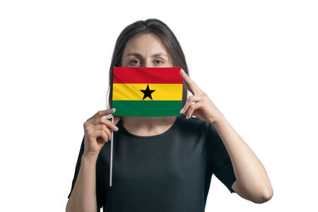 Happy young white woman holding flag Ghana flag and covers her face with it isolated on a white background.