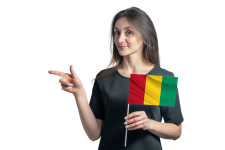 Happy young white woman holding flag Guinea and points to the left isolated on a white background. 免版税图像