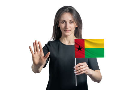 Happy young white woman holding flag of Guinea-Bissau and with a serious face shows a hand stop sign isolated on a white background. 免版税图像