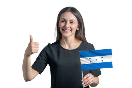 Happy young white woman holding flag of Honduras and shows the class by hand isolated on a white background.