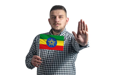 White guy holding a flag of Ethiopia and with a serious face shows a hand stop sign isolated on a white background.