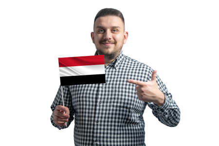 White guy holding a flag of Yemen and points the finger of the other hand at the flag isolated on a white background.