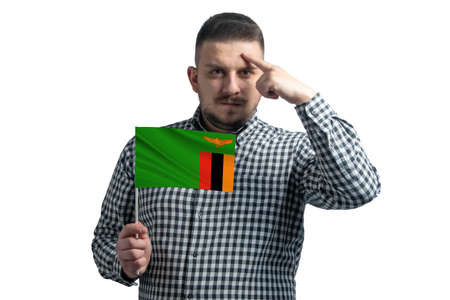 White guy holding a flag of Zambia and a finger touches the temple on the head isolated on a white background. 免版税图像