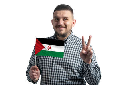White guy holding a flag of Western Sahara and shows two fingers isolated on a white background. 免版税图像