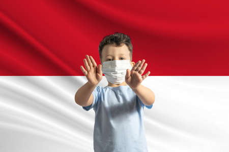 Little white boy in a protective mask on the background of the flag of Indonesia Makes a stop sign with his hands, stay at home Indonesia. 免版税图像