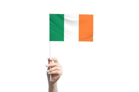 Beautiful female hand holding Ireland flag, isolated on white background. 免版税图像