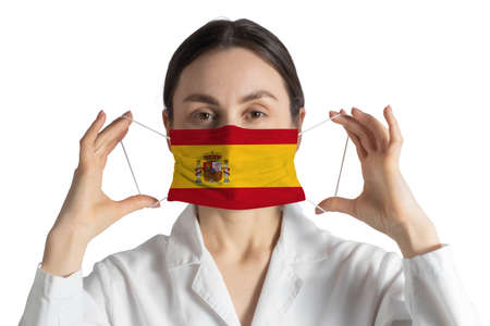 Respirator with flag of Spain Doctor puts on medical face mask isolated on white background. 免版税图像