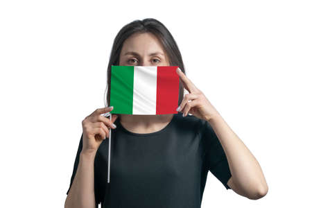 Happy young white woman holding flag Italy flag and covers her face with it isolated on a white background. 免版税图像