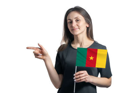 Happy young white woman holding flag Cameroon and points to the left isolated on a white background. 免版税图像