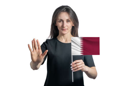 Happy young white woman holding flag of Qatar and with a serious face shows a hand stop sign isolated on a white background.