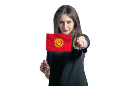 Happy young white woman holding flag of Kyrgyzstan and points forward in front of him isolated on a white background. 免版税图像