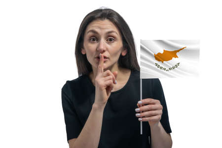 Happy young white woman holding flag of Cyprus and holds a finger to her lips isolated on a white background. 免版税图像