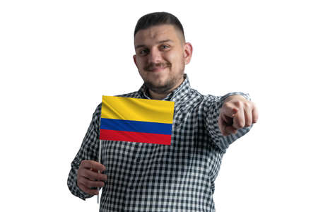 White guy holding a flag of Colombia and points forward in front of him isolated on a white background.