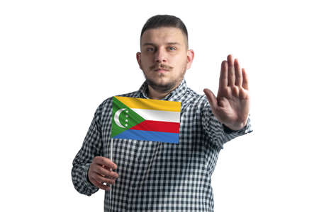 White guy holding a flag of Comoros and with a serious face shows a hand stop sign isolated on a white background. 免版税图像