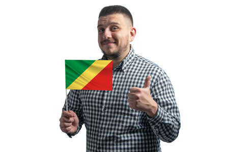 White guy holding a flag of Republic of the Congo and shows the class by hand isolated on a white background. Like for Republic of the Congo.
