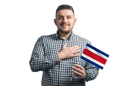 White guy holding a flag of Costa Rica and holds his hand on his heart isolated on a white background With love to Costa Rica. 免版税图像