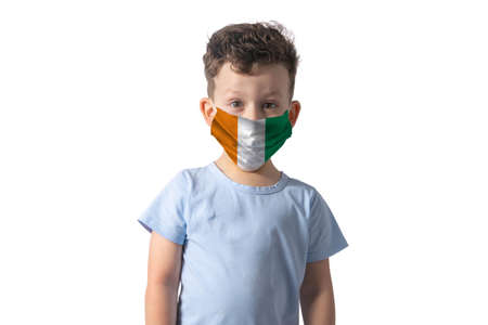 Respirator with flag of Cote d'Ivoire White boy puts on medical face mask isolated on white background.