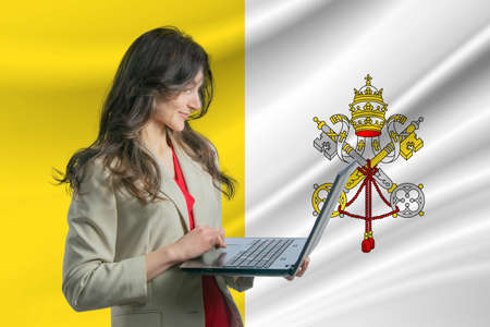 Freelance in Vatican. Beautiful young woman freelancer uses laptop against the background of the flag of Vatican