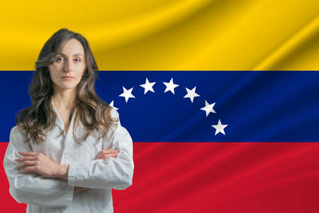 Medicine in Venezuela. Happy beautiful female doctor in medical coat standing with crossed arms against the background of the flag of Venezuela