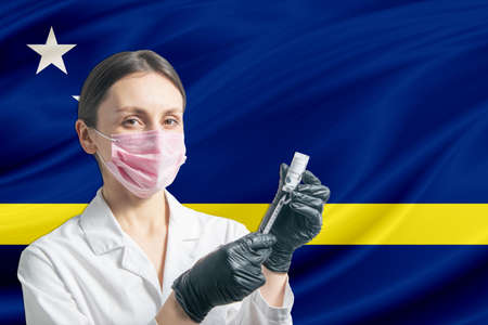 Girl doctor prepares vaccination against the background of the Curacao flag. Vaccination concept Curacao.