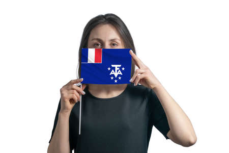 Happy young white woman holding flag French Southern and Antarctic Territories flag and covers her face with it isolated on a white background.