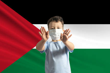 Little white boy in a protective mask on the background of the flag of Palestinian state. Makes a stop sign with his hands, stay at home Palestinian state.