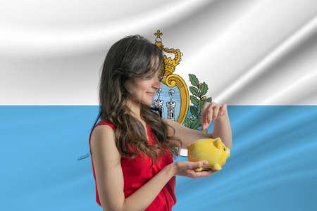 Economy in San Marino. Accumulating and saving money in San Marino. Woman putting money coin in piggy bank for saving money and plan finance