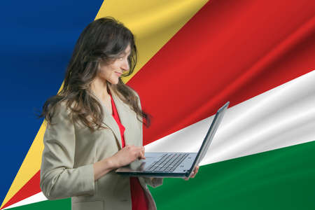 Freelance in Seychelles. Beautiful young woman freelancer uses laptop computer against the background of the flag of Seychelles