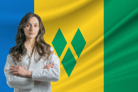 Medicine in Saint Vincent and the Grenadines. Happy beautiful female doctor in medical coat standing with crossed arms against the background of the flag of Saint Vincent and the Grenadines 写真素材