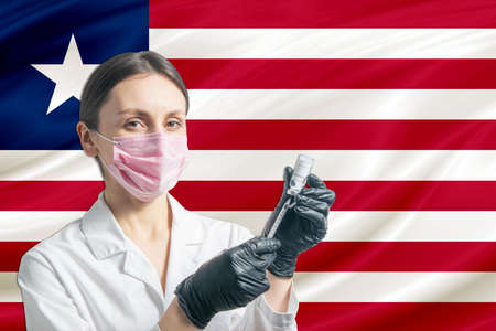 Girl doctor prepares vaccination against the background of the Liberia flag. Vaccination concept Liberia.