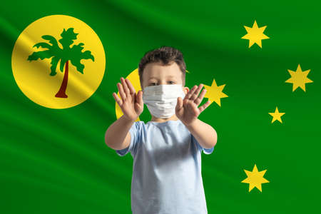 Little white boy in a protective mask on the background of the flag of Cocos Islands. Makes a stop sign with his hands, stay at home Cocos Islands.