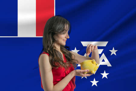 Economy in French Southern and Antarctic Territories. Accumulating and saving money in French Southern and Antarctic Territories. Woman putting money coin in piggy bank for saving money and plan finance