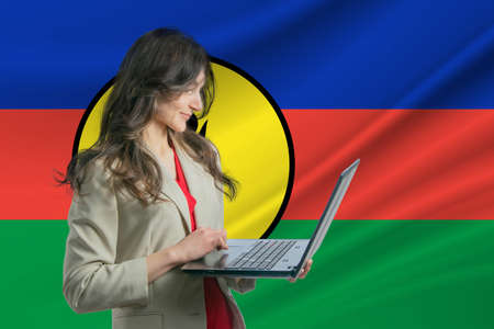 Freelance in New Caledonia. Beautiful young woman freelancer uses laptop computer against the background of the flag of New Caledonia 写真素材