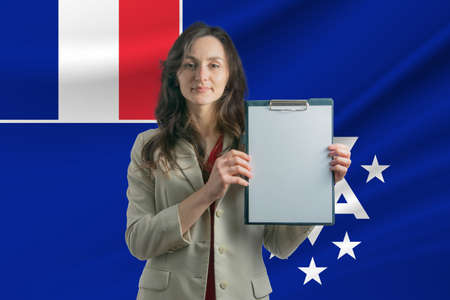 Study in French Southern and Antarctic Territories. Beautiful woman holding a sheet of paper in her hands. Girl on the background of the flag of French Southern and Antarctic Territories