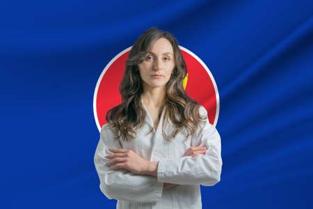 Medicine in Association of Southeast Asian Nations. Happy beautiful female doctor in medical coat standing with crossed arms against the background of the flag of Association of Southeast Asian Nations 写真素材