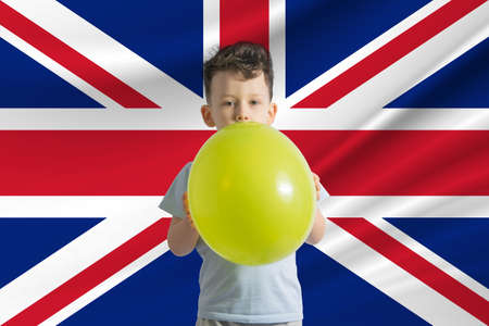 Children's day in United Kingdom. White boy with a balloon on the background of the flag of United Kingdom. Childrens day celebration concept.