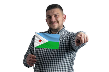 White guy holding a flag of Djibouti and points forward in front of him isolated on a white background.