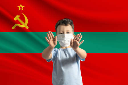 Little white boy in a protective mask on the background of the flag of Transnistria. Makes a stop sign with his hands, stay at home Transnistria.