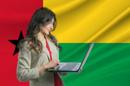 Freelance in Guinea-Bissau. Beautiful young woman freelancer uses laptop computer against the background of the flag of Guinea-Bissau.