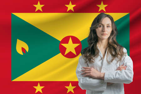 Medicine in Grenada. Happy beautiful female doctor in medical coat standing with crossed arms against the background of the flag of Grenada.