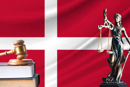 Law and justice in Denmark. Statue of themis and the gavel of the judge against the background of the flag of Denmark.
