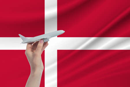 Airplane in hand with national flag of Denmark. Travel to Denmark.